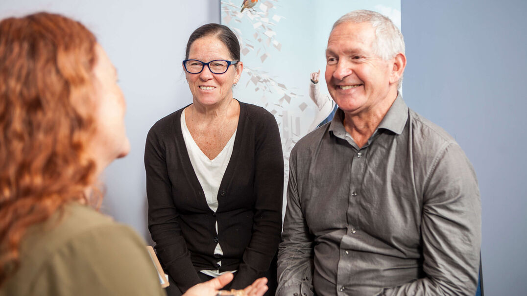 Smiling couple are having a conversation with an audiologist who is holding a hearing aid