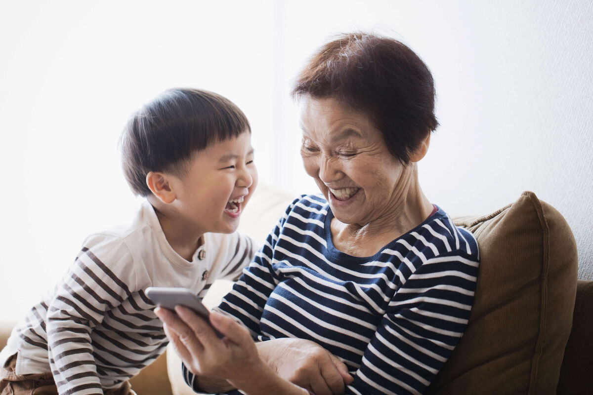 A grandmother a her toddler grandson are laughing while looking at a smart phone. If your hearing challenges are impacting your relationships Expression Audiology can help.