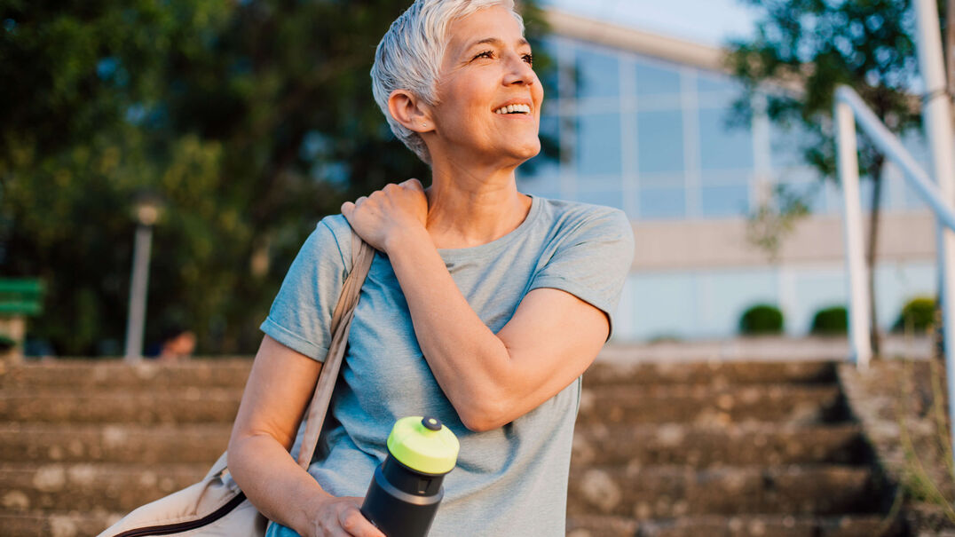 A woman smiles as she is bathed in golden sunshine. She is carrying a water bottle, suggesting she has been exercising. Don't let tinnitus cast a shadow over your life, talk to someone who understands at Expression Audiology.