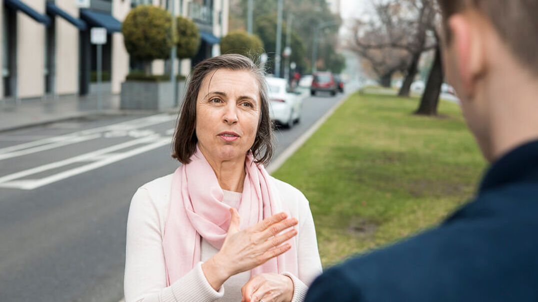 A woman wearing a pink scarf is having a conversation with a man using Auslan. The are standing on a grassy area next to a city street. Learn Auslan with Expression Australia.