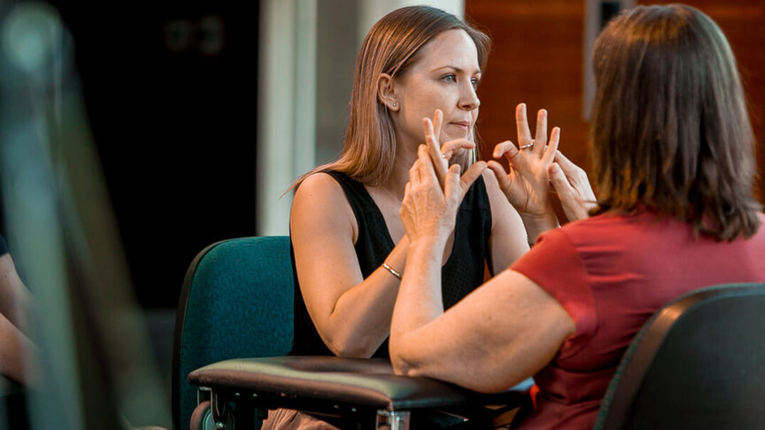 An interpreter is interpreting for a woman who is Deafblind. The interpreter signs in Auslan and the woman gently touches the interpreter's hands so she can feel what is being signed.