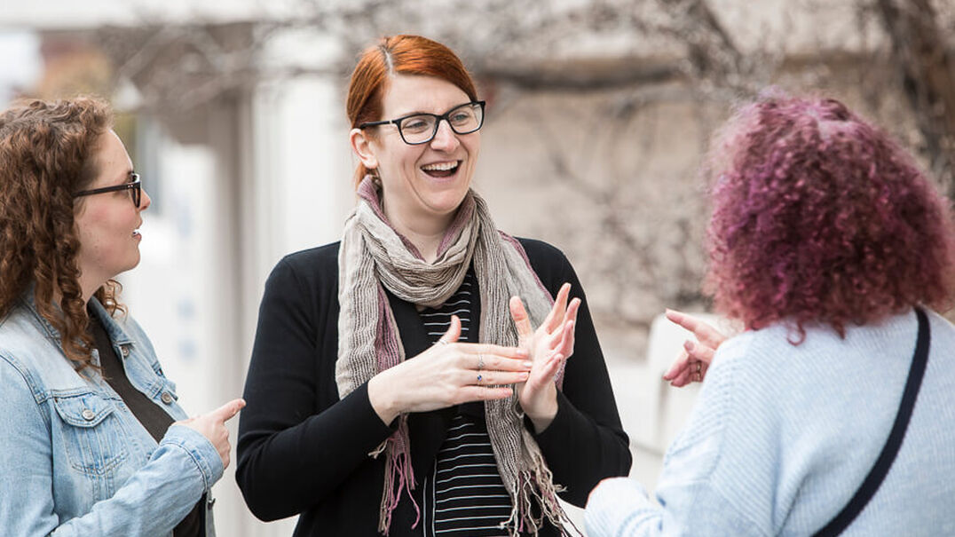 Three women are smiling as they have a friendly conversation using Auslan.