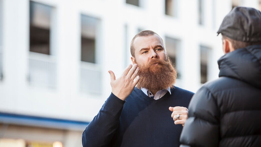 A man with a large but well maintained beard uses Auslan as he talks to another man in a street in front of a building. It's cold because the other man is wearing a cap and large jacket.